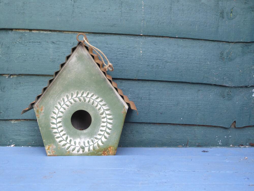 Vogelhaus aus Metall auf dem Boden
